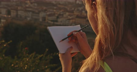 maria : Tourist girl drawing from nature at sunset in Florence city. Travel, art, tourism, lifestyle, urban concept. Filmed on RED 4k, 12 bit color
