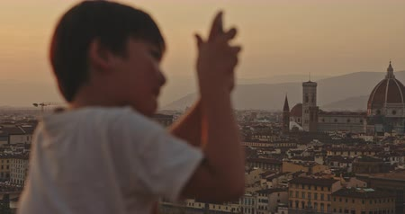 maria : Tourist boy taking picture of Florence standing at viewpoint at sunset time. Travel, tourism, lifestyle, urban concept. Filmed on RED 4k, 12 bit color