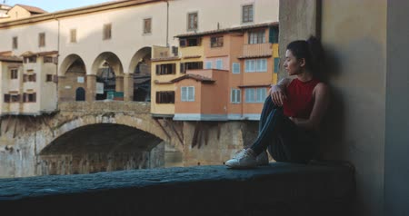 vecchio : Asian girl in Florence with Ponte Vecchio bridge and Arno river on the background. Portrait of young woman visiting. Travel, lifestyle, urban concept. Filmed on RED 4k, 12 bit color
