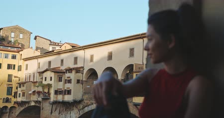 посещающий : Tourist asian girl in Florence with Ponte Vecchio bridge and Arno river on the background. Portrait of young woman visiting. Travel, lifestyle, urban concept. Filmed on RED 4k, 12 bit color