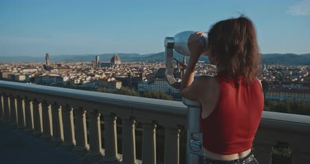 firenze : Female asian tourist looking at Florence city through binoculars afrom the viewpoint . Travel, tourism, lifestyle, urban concept. Filmed on RED 4k, 12 bit color