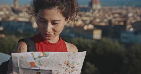renaissance : Tourist woman browsing through the map of Florence city with great background. Travel, tourism, lifestyle, urban concept. Filmed on RED 4k, 12 bit color