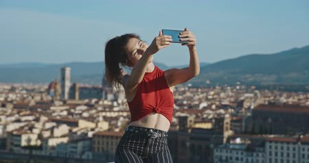 жестокий : Body positive woman with a scar on her belly taking selfie on background of Florence. Travel, body positive, tourism, lifestyle, urban concept. Filmed on RED 4k, 12 bit color Стоковые видеозаписи