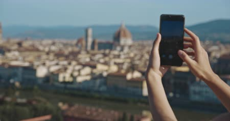 maria : Tourist woman taking picture of Florence standing at viewpoint at sunset time. Travel, tourism, lifestyle, urban concept. Filmed on RED 4k, 12 bit color