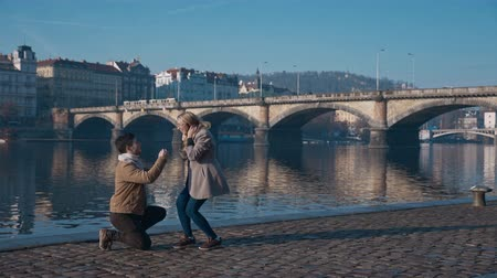 engaged : Young man in love standing on one knee and holding a ring while proposing to girlfriend on pier. Love, family, relationship, wedding concept. Filmed on REd 4k, 10 bit color