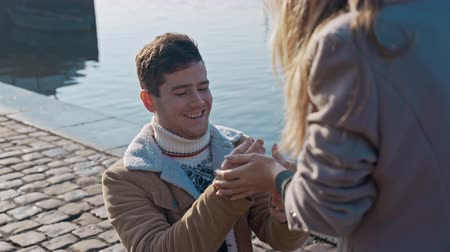 engaged : Handsome young man in love standing on one knee and holding a ring while proposing to girlfriend on pier. Love, family, relationship, wedding concept. Filmed on REd 4k, 10 bit color