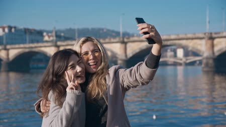 grimacing : Two lesbian friends taking selfie in Prague city. Pride, lgbt, love wins, tolerance, gay concept. Filmed on REd 4k, 10 bit color