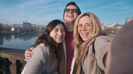 un : Happy friends taking selfe in Prague. Travel, friendship, youth, millenial, blogger, fame social media concept. Filmed on REd 4k, 10 bit color
