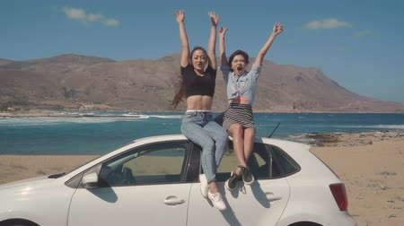 lesbijki : Two girls sitting on a roof of a car with hands raised. Freedom, vacation, friendship, tourism concept. Filmed on RED 4k, 10 bit color.