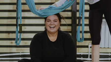 liberated : Happy body positive woman smiling and laughing after doing stretching exercise on hammocks. Boby positve, open mind, sport conncept. Filmed on RED 4K, 10 bit color.