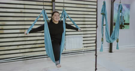 liberated : Cheerful body positive woman doing stretching exercise on hammocks and laughing. Boby positve, open mind, sport conncept. Filmed on RED 4K, 10 bit color. Stock Footage