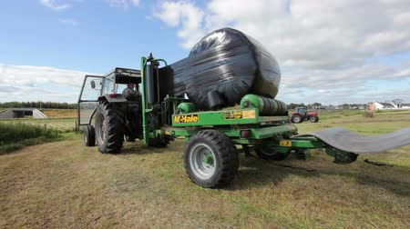 trator : Tractor wrapping bail of hay with plastic at the field Vídeos