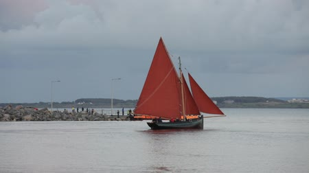 hooker : Traditional wooden boat Galway Hooker, with red sail leaving Galway docks in the evening. Ireland.