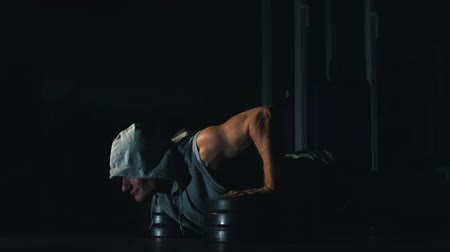 biceps : the athlete pushes, squeezes from the floor. Black background.