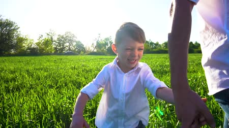 menino : little boy walking on the green field with his father Stock Footage