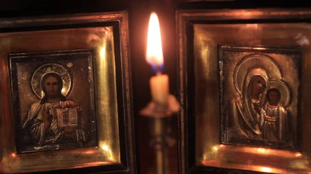 iconography : light a candle in front of the icons of Jesus and the Mother of God Stock Footage