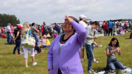 olhares : NOVOSIBIRSK, RUSSIA - JULY 26, 2015: Woman looking the sky with her hand on forehead. Outdoor public event. Airshow
