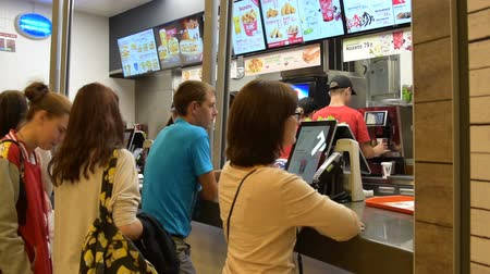 фастфуд : NOVOSIBIRSK, RUSSIA AUGUST 14, 2015: Hungry people waiting for their turn to buy fast food in KFC, one of the most popular fast food restaurants in the world Стоковые видеозаписи