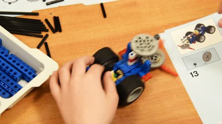 sınıf : Close-up shot of a boy finishing toy robot and trying how it will work. Studying robotics at school Stok Video