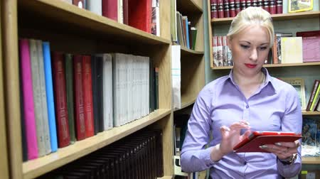 szukanie : Girl using a tablet computer to find the name of the book and then searching for it on the library shelf