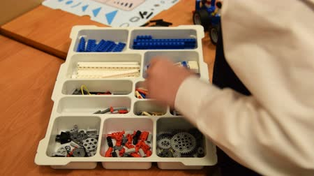 sınıf : Pupil putting robot parts in the box with meccano set. Robotics class at school