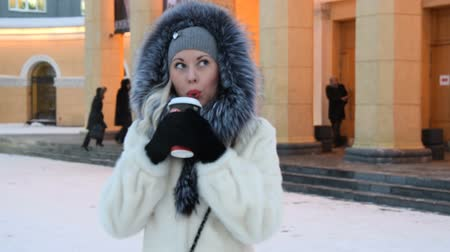 cold : Young blonde in fur coat drinking coffee in city street in winter evening