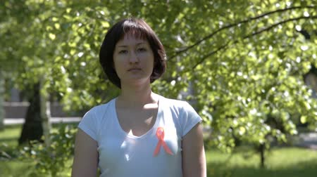 self injury : Young brunnete woman in white t-shirt wearing orange ribbon, trees background. Leukemia, melanoma, multiple sclerosis, Self Injury Awareness Day
