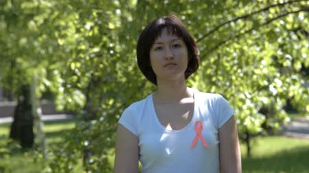self injury : Woman pinning orange ribbon on white t-shirt, trees in background. Leukemia, melanoma, multiple sclerosis, Self Injury Awareness Day