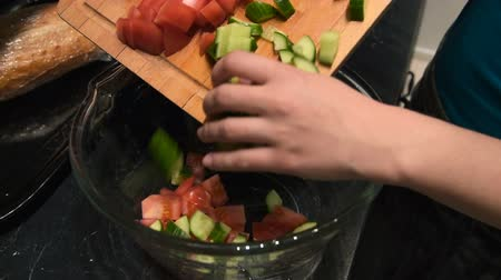 chop up : Putting chopped fresh cucumbers and tomatoes into the bowl. Making vegetarian salad Stock Footage