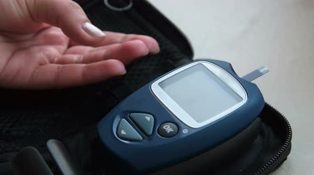 zkontrolovat : Close-up shot of woman pricking finger with lancing device and taking blood sugar level test with glucometer. Normal range on display Dostupné videozáznamy