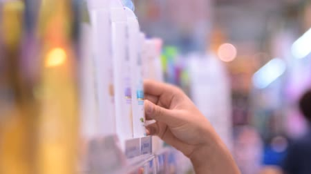 şampuan : Close-up shot of woman choosing shampoo in the supermarket Stok Video