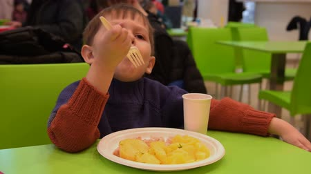 Little boy eating potatoes with meat in food court of shopping mall