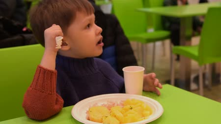 Little boy eating potatoes with meat in food court of shopping centre Стоковые видеозаписи
