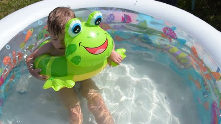 žába : Little kid bathing and having fun with rubber frog in outdoor pool. Water fun on summer day Dostupné videozáznamy