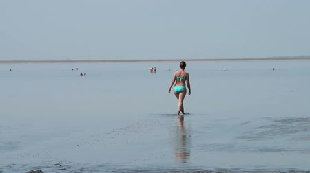 Young woman walking in the mud of salty-bitter Lake Karachi in Siberia, Russia. Natural resort and recreation