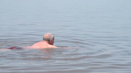 afloat : Senior man bathing in salty lake. Natural resort and recreation