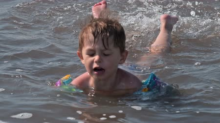 Funny little boy with ater wings trying to swim in salty lake and splashing water with feet. Active and healthy kid