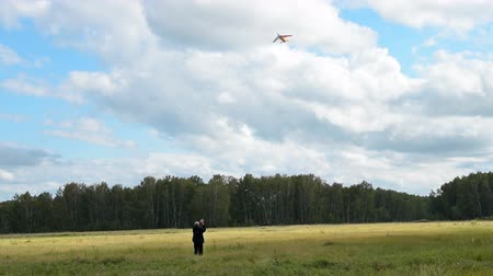 Happy senior man flying rainbow kite in the countryside. Active leisure in retirement Стоковые видеозаписи