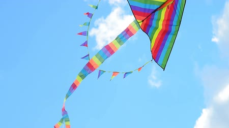 Big Rainbow coloured kite hovering in strong wind against blue sky