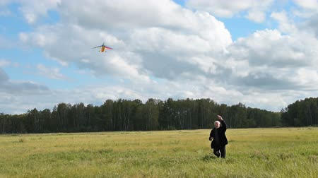 Happy senior man leading active lifestyle and flying kite in the countryside in his free time