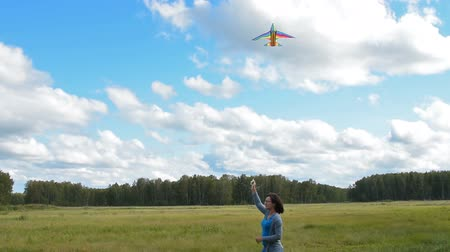 Young woman leading active lifestyle and flying kite in the countryside in her free time