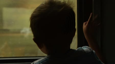 Little boy traveling by train and looking out the window Стоковые видеозаписи