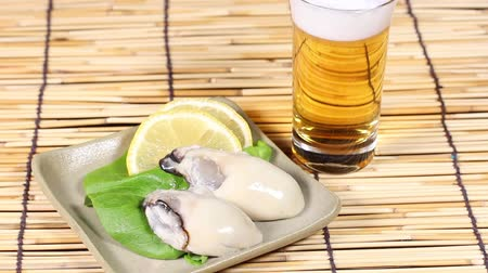 bamboo curtain : Glass of beer and fresh raw oyster Stock Footage