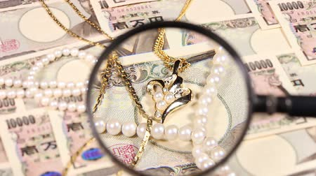 ten : Japanese yen bill and magnifying glass and jewelry Stock Footage
