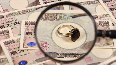 богатый : Japanese yen bill and magnifying glass and jewelry Стоковые видеозаписи