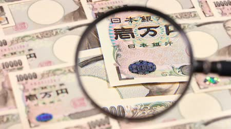 процветание : Japanese yen bill and magnifying glass