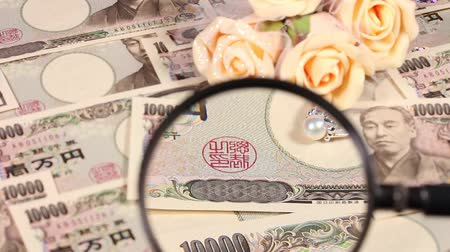 appraisal : Japanese yen bill and magnifying glass and ring