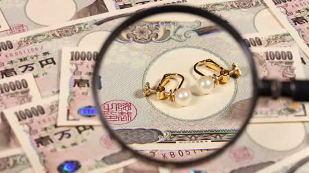 appraisal : Japanese yen bill and magnifying glass and earring