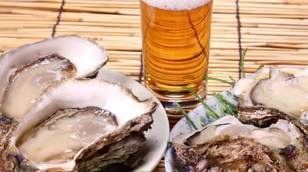 bamboo curtain : Fresh oysters and glass of beer Stock Footage
