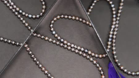 prestigious : Black pearl necklace and rosary reflecting in the mirror